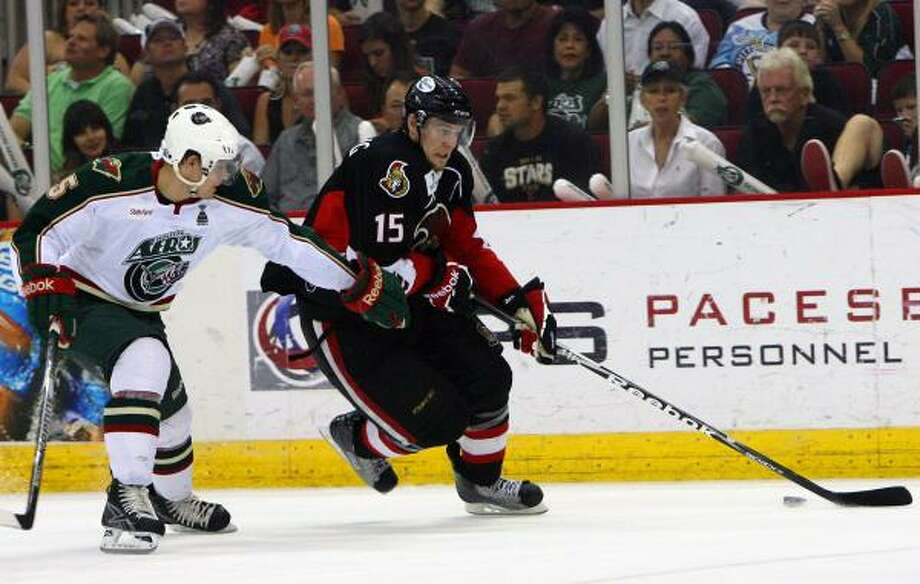 Binghamton Senators left wing Colin Greening (15) skates past Houston Aeros defenseman Jeff Penner (5) as he attempts to score. Photo: Cody Duty, Chronicle