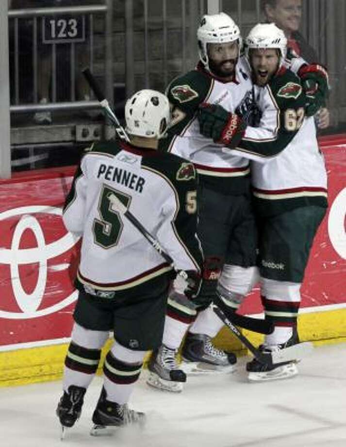 Houston Aeros Jeff Penner (5), Robbie Earl (center) and Jean-Michel Daoust (62) celebrate after Daoust scored a goal on Binghamton Senators goalie Robin Lehner. Photo: Cody Duty, Chronicle