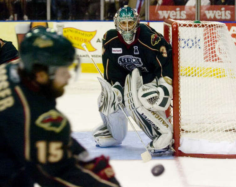 Houston Aeros' (31) Matt Hackett eyes the puck as teammate (15) Nate Prosser moves in to defend.