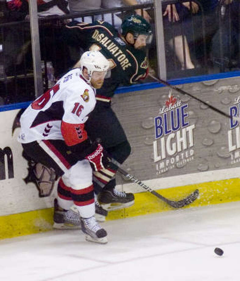 Binghamton Senators' (16) Cody Bass and Houston Aeros' (14) Jon DiSalvatore clash at the boards. Photo: REBECCA CATLETT, Press & Sun-Bulletin