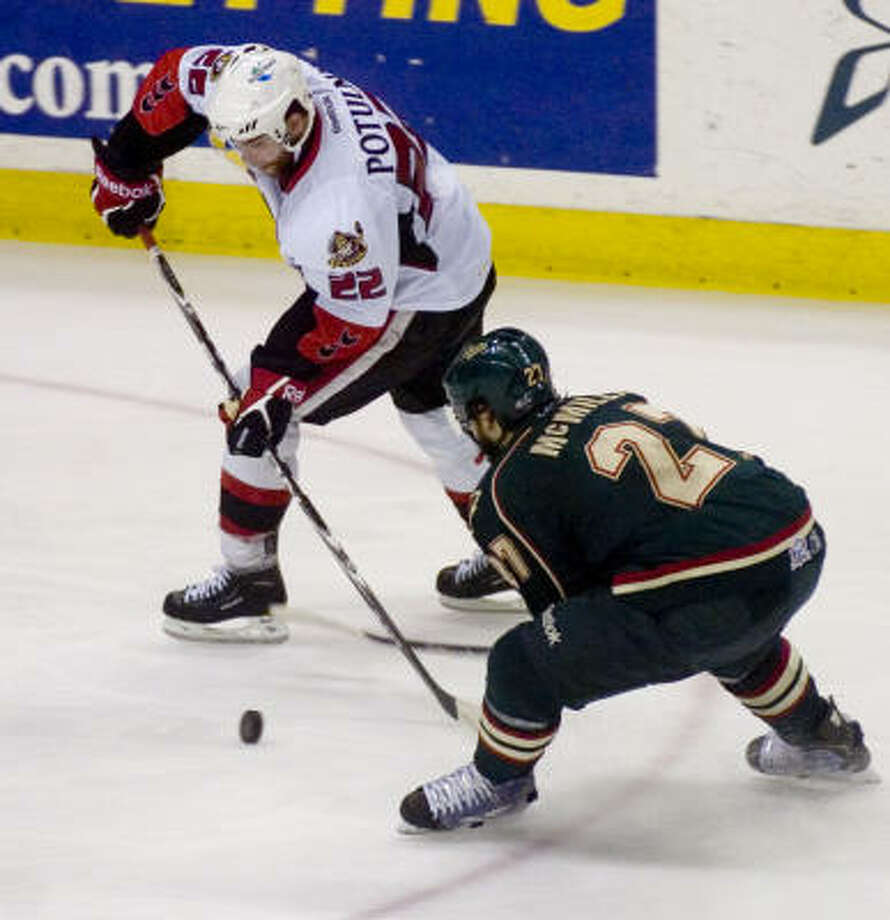 Binghamton Senators' (22) Ryan Potulny is pressured by Houston Aeros' (27) Carson McMillan in the third period. Photo: REBECCA CATLETT, Press & Sun-Bulletin