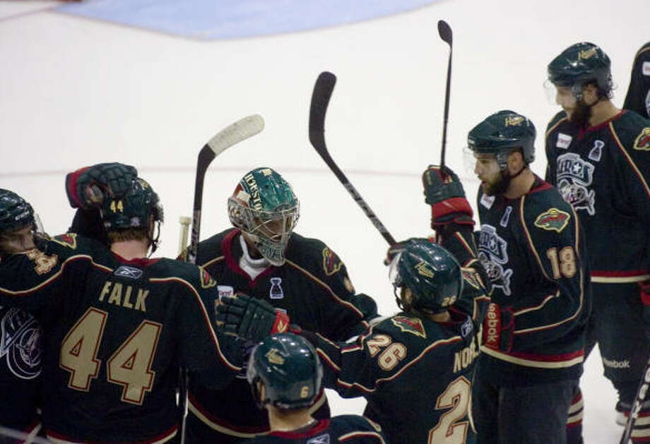 Houston Aeros' (31) Matt Hackett celebrates the victory with his teammates. Photo: REBECCA CATLETT, Press & Sun-Bulletin