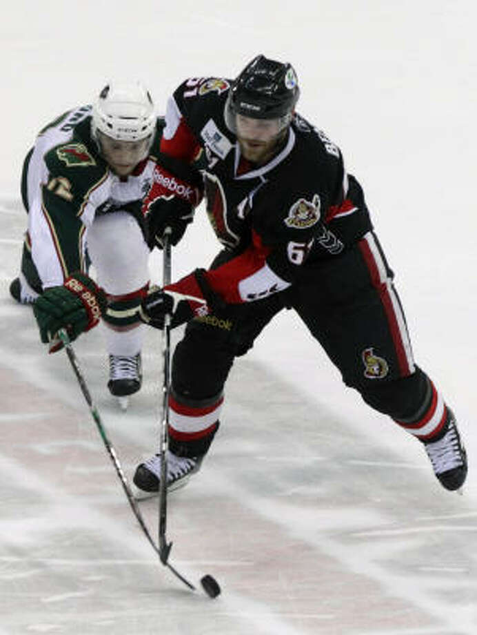 Aeros center Cody Almond (12) reaches for the puck as Binghamton Senators defenseman Andre Benoit takes possession in the second period. Photo: Cody Duty, Chronicle