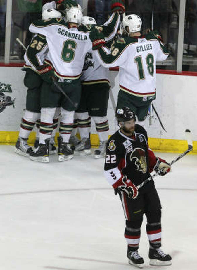 The Aeros celebrate right wing Jed Ortmeyer's third-period goal as Senators center Ryan Potulny (22) looks on in the third period. Photo: Cody Duty, Chronicle