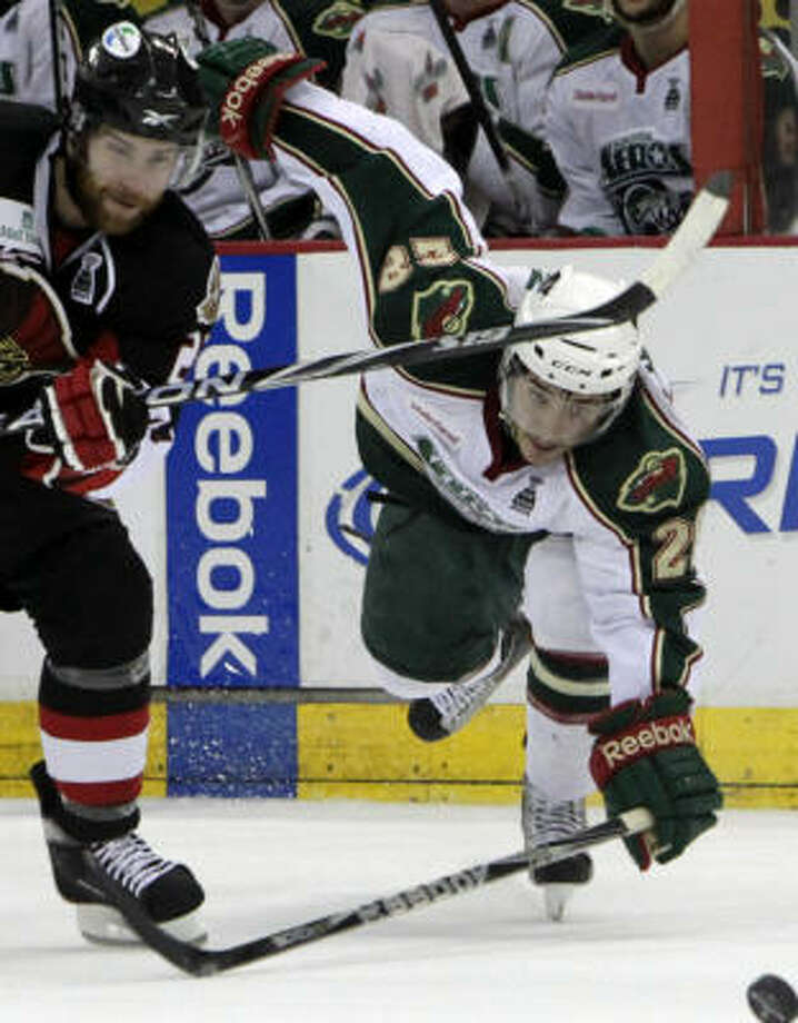 Aeros defenseman Jared Spurgeon, right, loses his balance as he and Binghamton Senators center Ryan Potulny look for possession of the puck in the first period. Photo: Cody Duty, Chronicle
