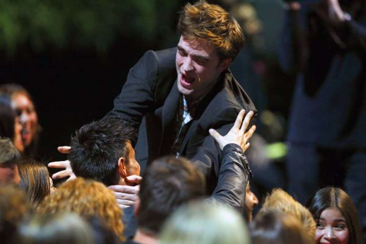 Robert Pattinson, right, reaches out to kiss Taylor Lautner at the MTV Movie Awards on Sunday, June 5, 2011, in Los Angeles. (AP Photo/Matt Sayles)