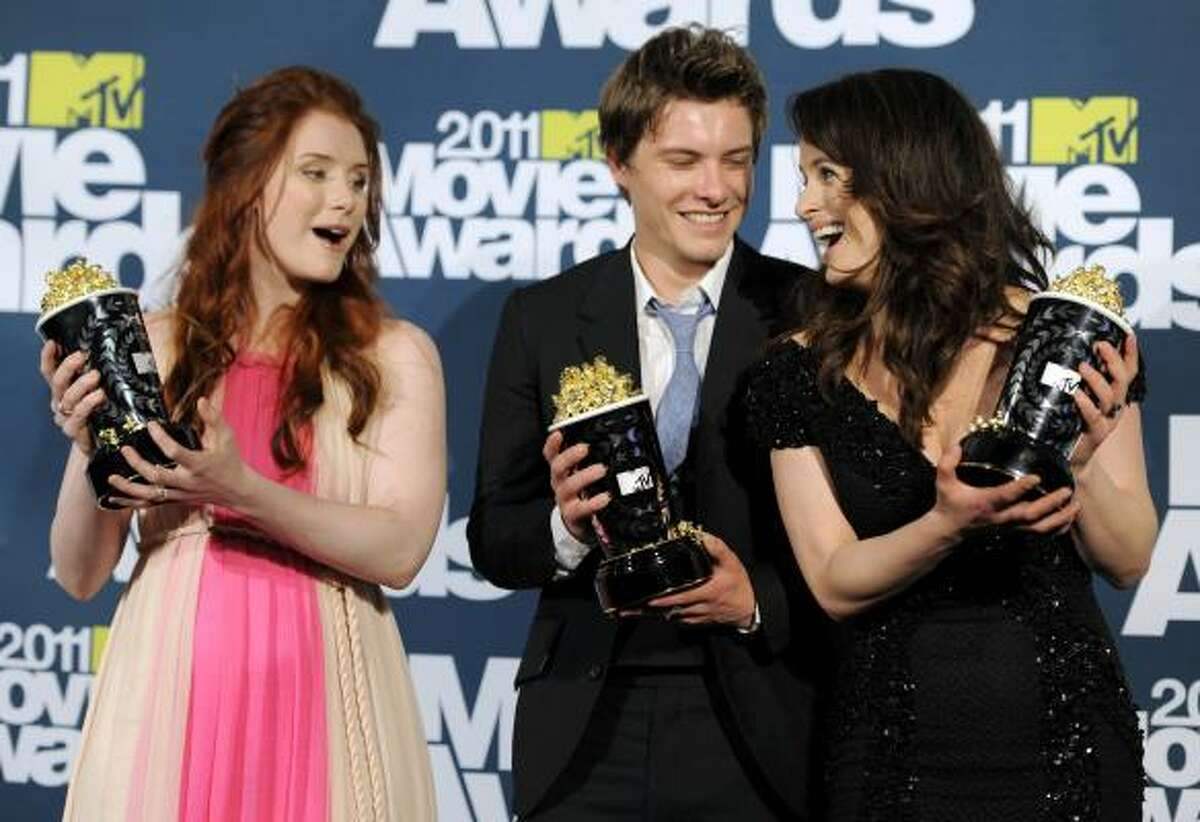 Bryce Dallas Howard, left, Xavier Samuel and Elizabeth Reaser get the golden popcorn as their film, Twilight Saga: Eclipse, wins Best Movie.