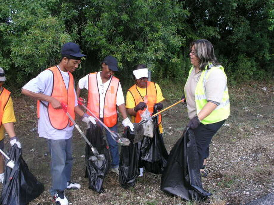 Quintin Washington, left, his mother, Mira Washington, Anna Davis and Marie Bolanos pitched in to help in the cleanup effort by picking up trash. Photo:  Fannie Williams, For The Chronicle