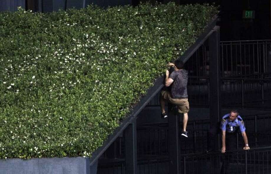 A fan eludes a police office by climbing onto the center field wall after running across the outfield and stopping play during the ninth inning. Photo: David J. Phillip, Associated Press