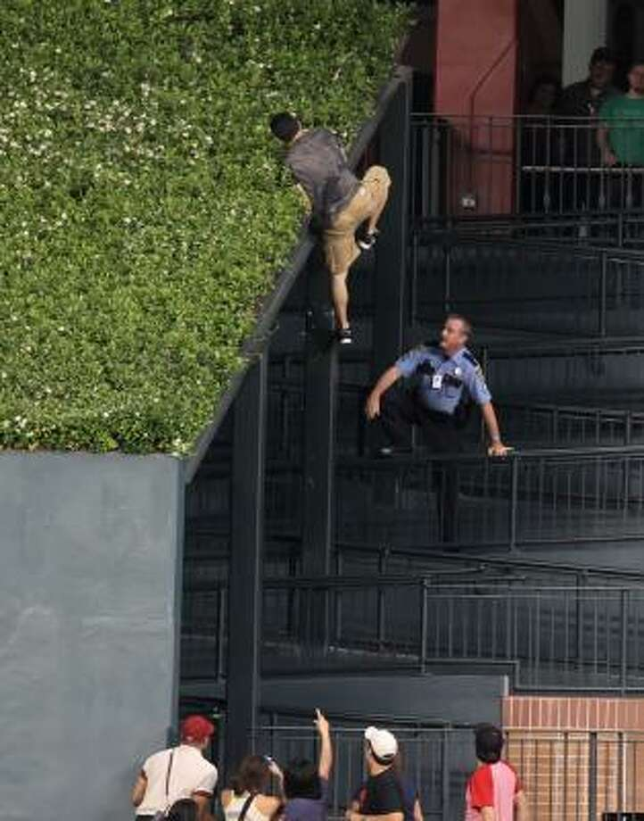 A fan eludes police by climbing onto the center-field greenery after running on the field and jumping the center field wall during the ninth inning. Photo: George Bridges, McClatchy-Tribune News Service