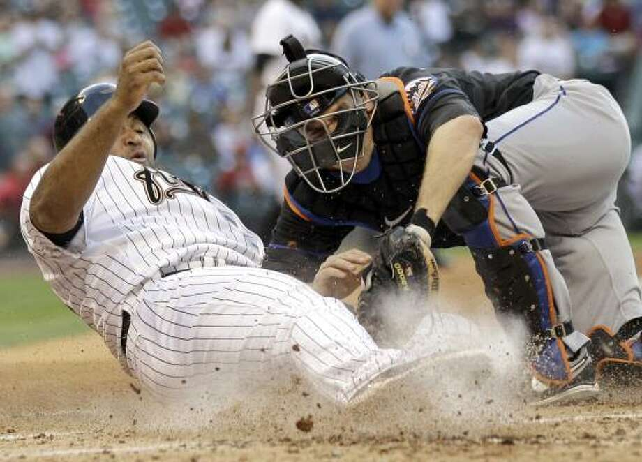Carlos Lee, left, is tagged out by Mets catcher Josh Thole while trying to score during the second inning. Photo: David J. Phillip, Associated Press