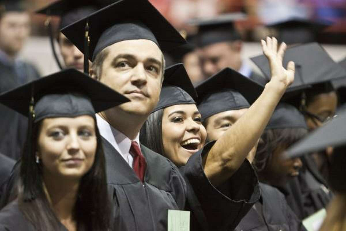 St. Thomas graduates look into the stands to find friends and relatives before commencement services for the University of St. Thomas in Houston at Reliant Arena.