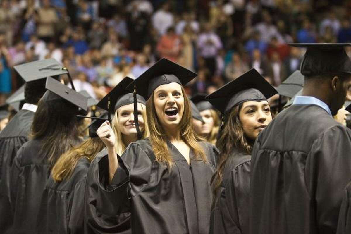 St. Thomas graduates look into the stands to find friends and relatives before commencement services for the University of St. Thomas.