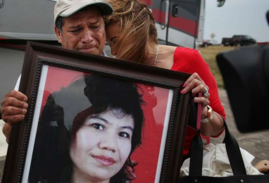 Angel Medina holds a photograph of his missing sister Senovia Medina while being embraced by Florenc