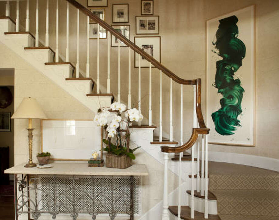 An entryway staircase becomes a focal point with rows of framed photos on its wall. A pot of orchids on the entry table enhances the look. Photo: Jill Hunter