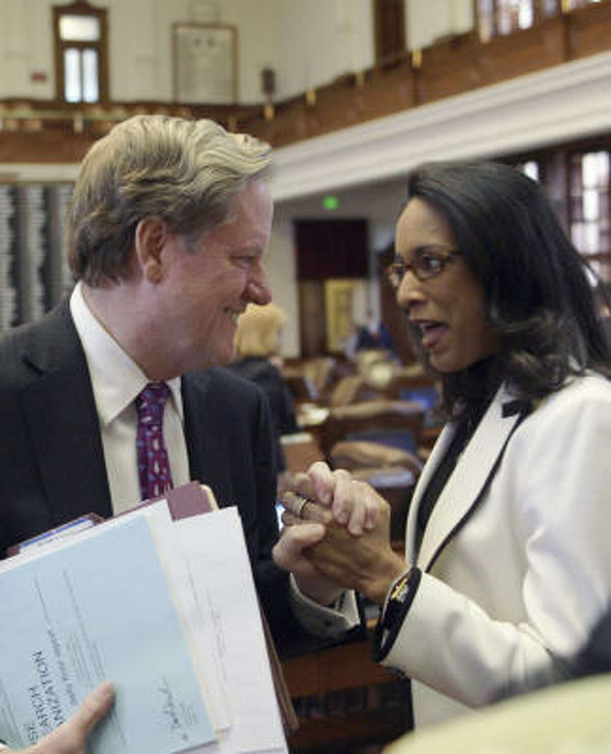 Rep. Jim Pitts, left, celebrates with Rep. Dawnna Dukes after a House panel approved the budget.