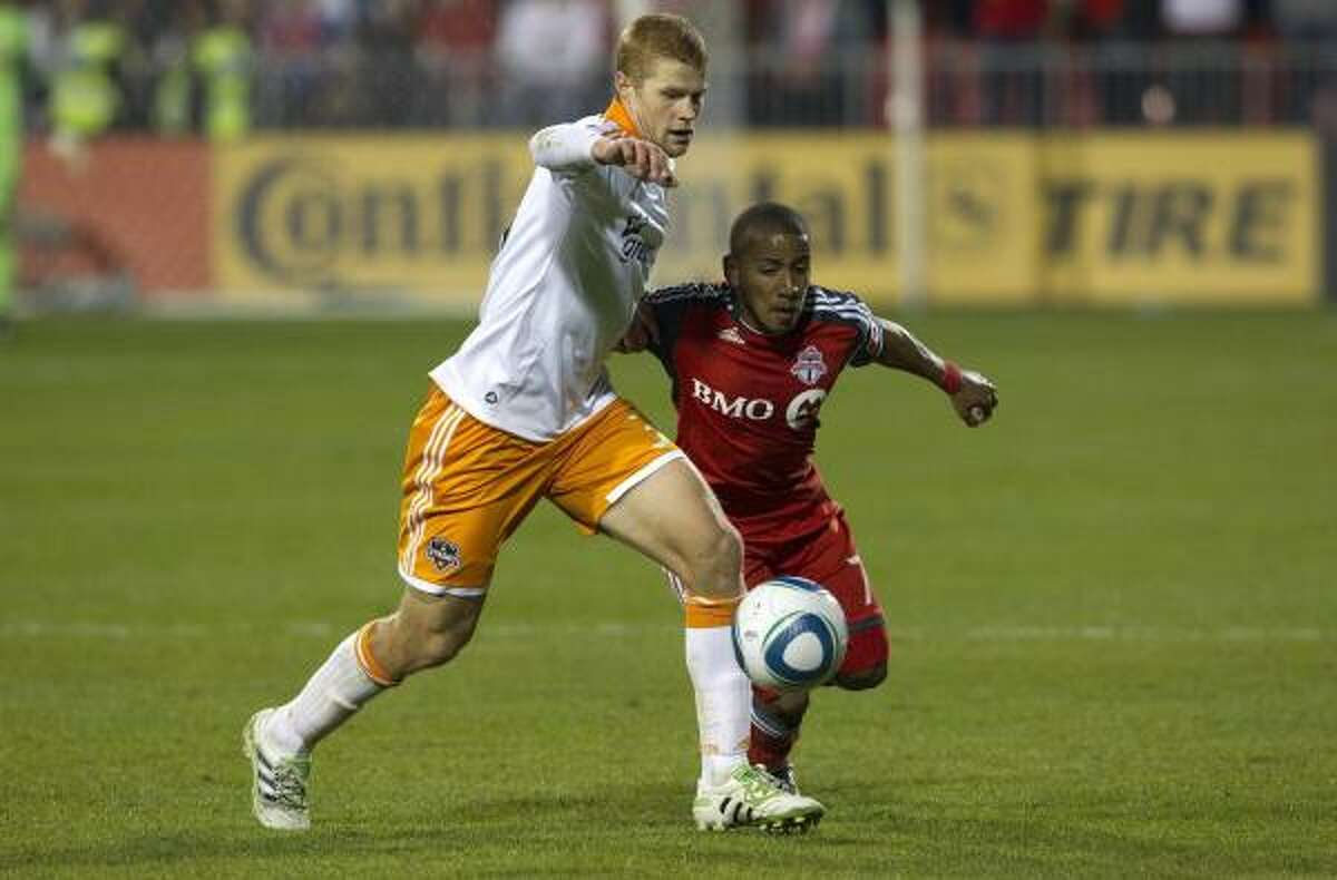 Toronto FC's Joao Plata, right, battles with Dynamo defender Andre Hainault during the second half.