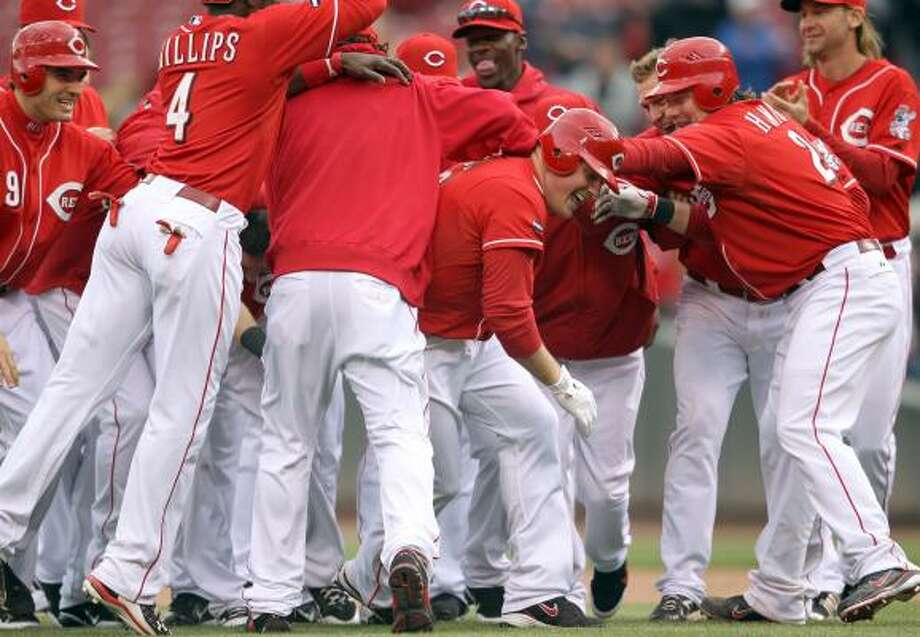 Reds players mob outfielder Jay Bruce after he drove in the winning run. Photo: Andy Lyons, Getty