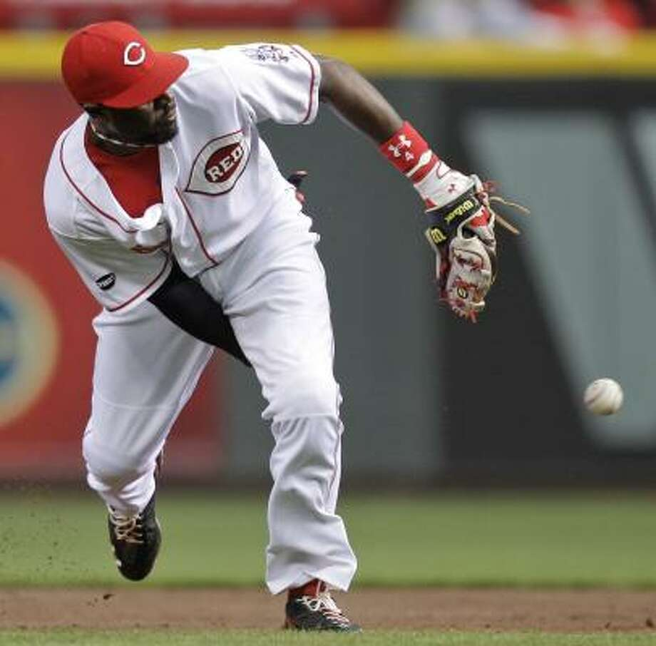Reds second baseman Brandon Phillips throws the ball between his legs to first base after fielding a ground ball hit by Jason Bourgeois in the third inning. Bourgeois was out at first. Photo: Al Behrman, Associated Press