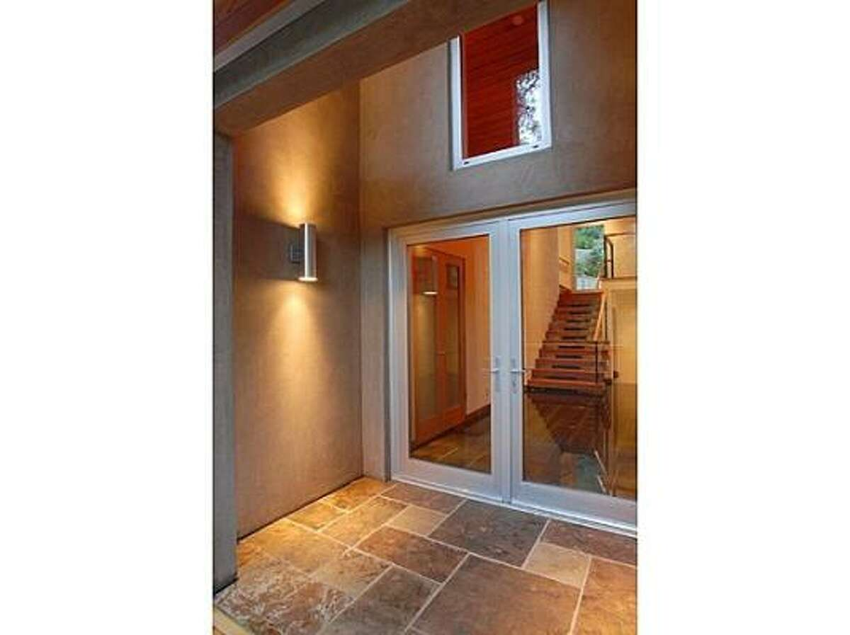The entrance of the home that was supposed to be Kutcher's bachelor pad has tile flooring and wide glass doors.