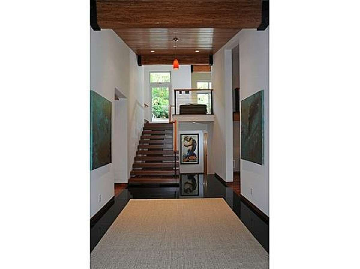 A wood beamed ceiling sits atop the foyer.