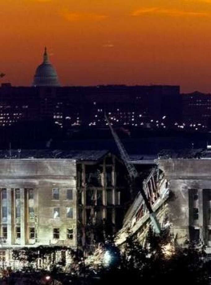 The sky glows orange as the sun rises over the damaged side of the Pentagon with the U.S. Capitol behind in Washington, Sept. 13, 2001. A hijacked airplane crashed into the Pentagon on Sept. 11, 2001, causing extensive damage. Photo: Luke Frazza, AFP