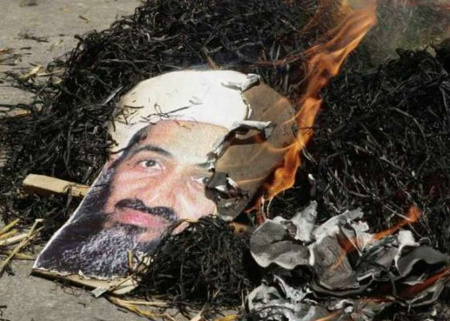 A portrait of Saudi dissident Osama bin Laden burns in New Delhi after protestors set alight his effigy during a protest against terrorism. The attacks on the U.S. launched worldwide vitriol against the leader. Photo: Mandel Ngan, AFP