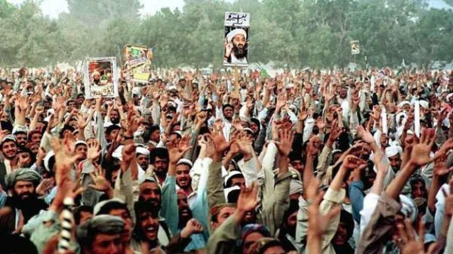 "Supporters display posters of suspected terrorist Osama bin Laden as they raise their hands to show their willingness to go to neighboring Afghanistan and fight against U.S. forces during an anti-U.S. rally in Quetta, Pakistan, Friday, Oct. 12, 2001. The word ""Hero"" is written in the poster in the center. Photo: Arshad Butt, AP"