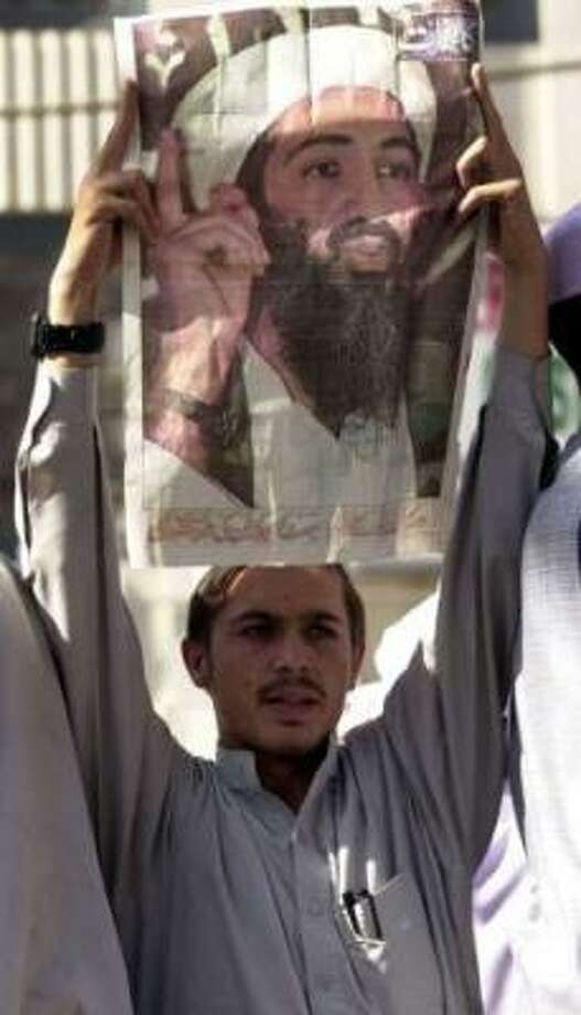 A Pakistani man holds a poster of Osama bin Laden during a rally in support of the Taliban and bin Laden and against the U.S. Friday Oct. 12, 2001 in Peshawar, Pakistan. A few thousand men took part in the event Photo: Edward A. Ornelas, San Antonio Express-News