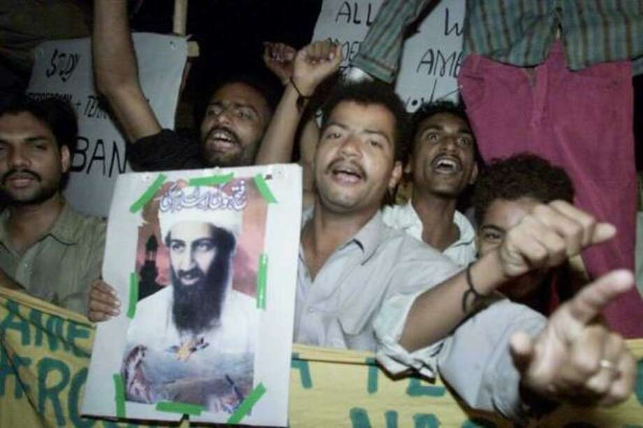 A small group of Pakistani supporters of the ruling Taliban in Afghanistan display a portrait of terrorist suspect Osama bin Laden as they stage a protest rally in Karachi, Pakistan, soon after the U.S.-led coalition attacked targets in Afghanistan late Sunday, Oct. 7, 2001. Photo: Zia Mazhar, AP