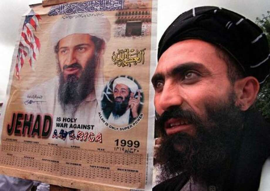 A religious protester holds a portrait of Saudi dissident Osama bin Laden during a protest rally against the United States, July 30, 1999 in Islamabad. Photo: Saeed Khan, AFP