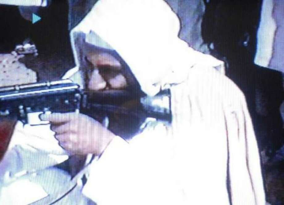 "A video grab dated 19 June 2001 shows Saudi dissident Osama bin Laden firing an AK-47 (Kalashnikov) sub-machine-gun in a video tape said to have been prepared and released by bin Laden himself. Copies of the tape, which shows members of bin Laden's organization Al-Qaeda, or ""The Base"", training at their al-Farouq base in Afghanistan, have been circulated to a limited number of Islamists. Photo: Yasser Al-Zayyat, AFP"
