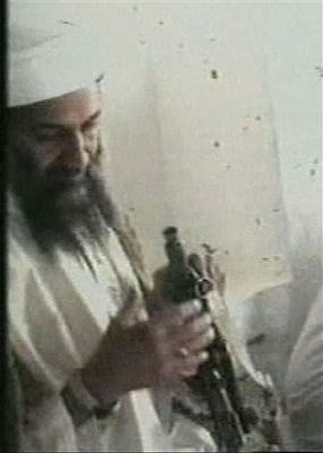 This television image released by Qatar's Al-Jazeera television broadcast on Friday Oct. 5, 2001 shows Osama bin Laden, left, handling a Kalshnikov rifle at an undisclosed location. Photo: AP