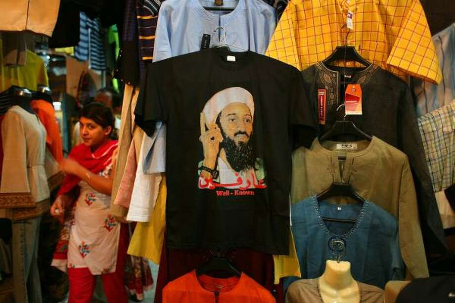 A t-shirt displaying the face of Al Qaeda leader Osama Bin Laden hangs for sale at a clothing market July 5, 2006 in Islamabad, Pakistan. Bin Laden remained a hero to a small minority in the Islamic world. Photo: John Moore, Getty Images