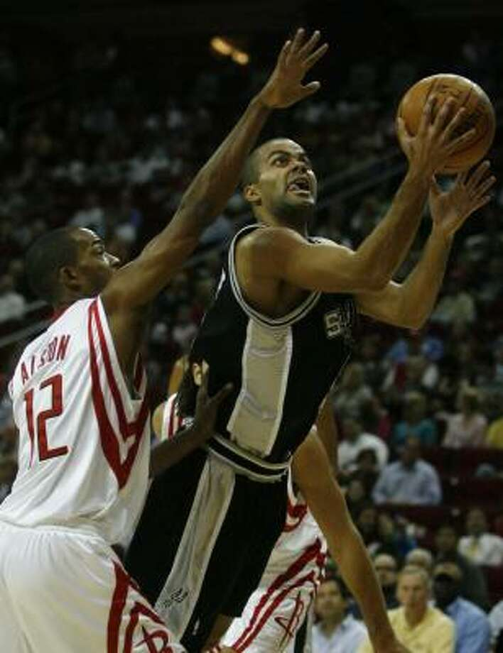 Rockets guard Rafer Alston (12) attempts to defend against Spurs guard Tony Parker during the first half Tuesday night at Toyota Center. Photo: Billy Smith II, Chronicle