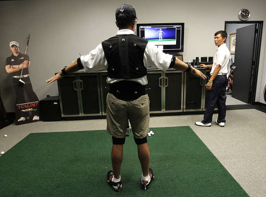Edwin Fuh, manager at the TaylorMade fitting lab at Redstone Golf Club, checks the placement of numerous reflective markers on Steven Hahn, as he gets ready to fit him for clubs. Photo: Karen Warren, Chronicle