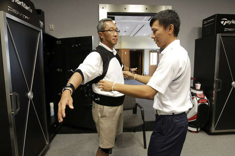 Edwin Fuh, manager at the TaylorMade fitting lab at Redstone Golf Club, adjusts the reflective markers on Steven Hahn's shoulders. Photo: Karen Warren, Chronicle