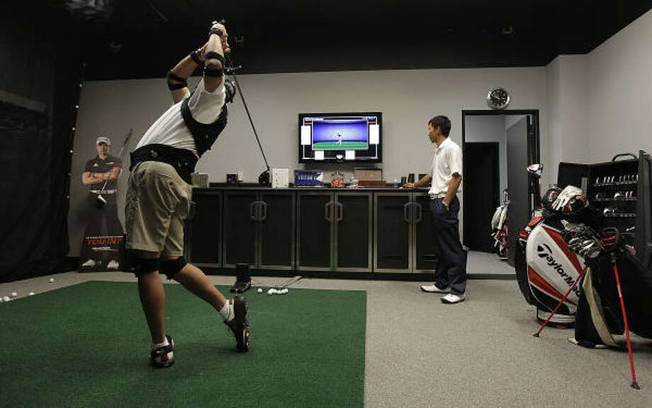 Edwin Fuh checks the monitor as Steven Hahn hits a ball. Photo: Karen Warren, Chronicle