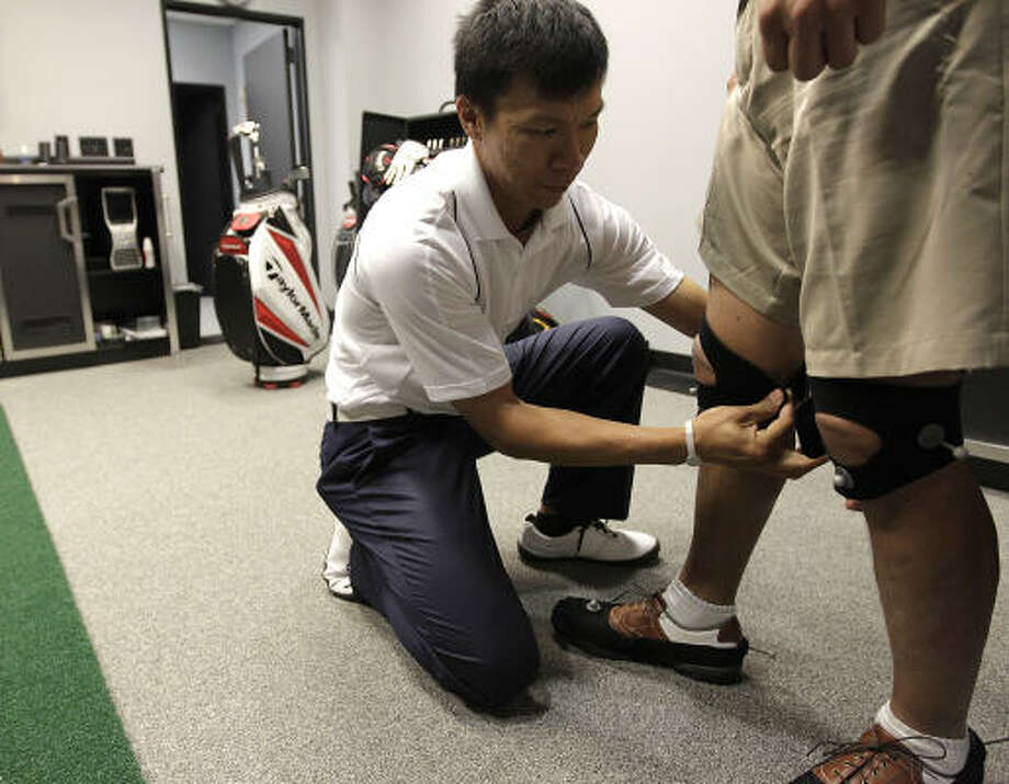 Edwin Fuh adjusts the reflective markers on Steven Hahn's knees. Photo: Karen Warren, Chronicle