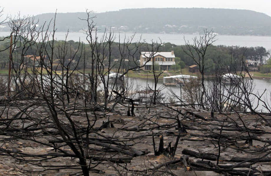 Burned trees are what is left at  Gaines Bend at Possum Kingdom Lake, Texas  on Thursday, April 21, 2011.   Crews have been trying to contain a week-old wildfire in the Possum Kingdom Lake area about 70 miles west of Fort Worth that has blackened nearly 150 square miles of fields and woods and destroyed at least 159 of the community's 3,000 homes. Photo: Louis DeLuca, AP