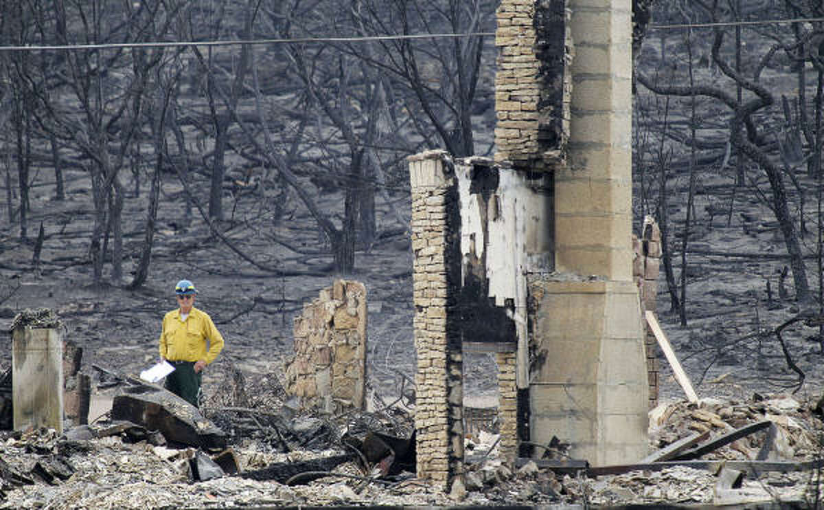 A member of a damage assessment team surveys the damage at Gaines Bend on Possum Kingdom Lake as officials still try to deal with the wildfires and their aftermath in Palo Pinto County west of Fort Worth, Thursday, April 21, 2011.