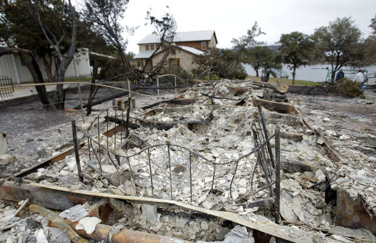 A home in the Gaines Bend neighborhood at Possum Kingdom Lake is burned to the ground but the one behind it appears unaffected Thursday, April 21, 2011.