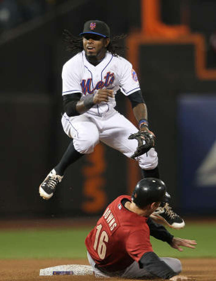 Mets infielder Jose Reyes turns a double play over the slide of Matt Downs. Photo: Nick Laham, Getty Images