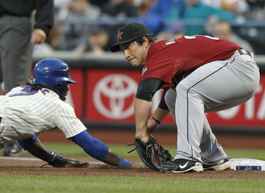 Mets' Jose Reyes (7) dives back to first base safely around the tag of Astros first baseman Brett Wallace on a pickoff attempt in the first inning. Photo: Paul J. Bereswill, AP