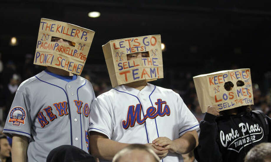 Three fans wear paper bags on their heads during the fourth inning. Photo: Paul J. Bereswill, AP