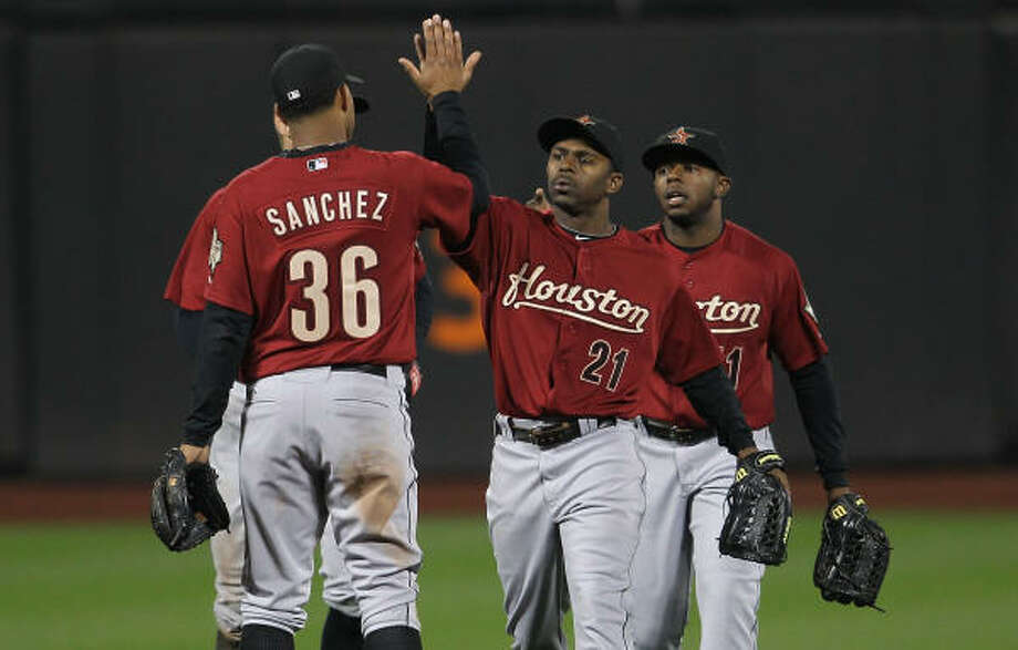 Michael Bourn (21) high-fives Angel Sanchez after Tuesday's 6-1 victory over the Mets. Photo: Nick Laham, Getty Images
