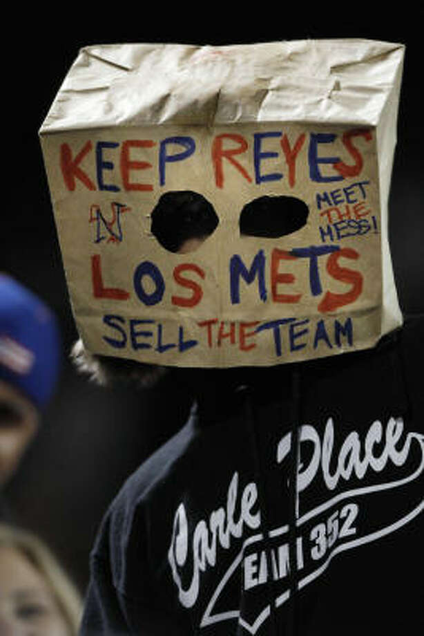A fan wears a paper bag over his head during the sixth inning. Photo: Frank Franklin II, AP