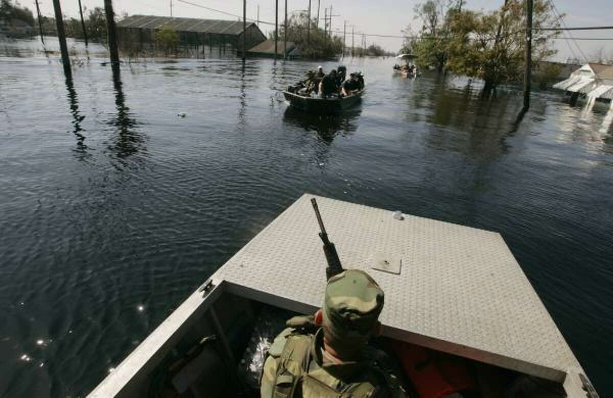 NEW ORLEANS - SEPTEMBER 7: Staff Sgt. Don Davis (R) of the Oklahoma National Guard patrols patrols a flooded neighborhood searching for Hurricane Katrina victims who didn't want to evacuate September 7, 2005 in New Orleans, Louisiana. The mayor of New Orleans ordered out the remaining holdouts in New Orleans, and said force would be used if neccessary.
