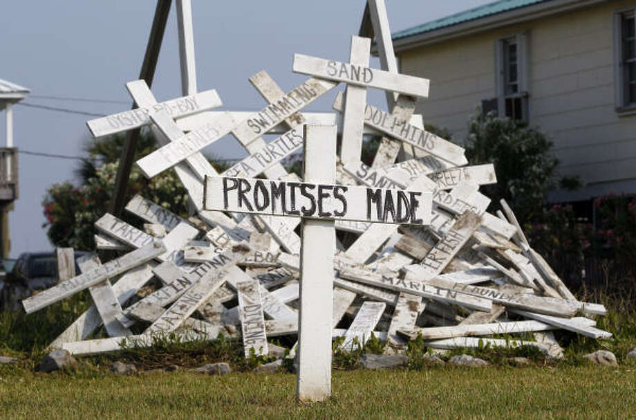 "A cross with the words ""promises made,"" referring to promises made by BP PLC and government officials responding to the Deepwater Horizon oil spill, stands in front of a pile of crosses symbolizing things that were impacted by the spill in a front yard in Grand Isle, La., Wednesday, April 20, 2011. One year after the nation's worst offshore oil spill began, solemn ceremonies will mark the disaster Wednesday and underscore the delicate healing that is only now taking shape. Photo: Patrick Semansky, AP"