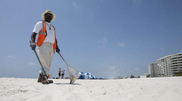 Oil spill cleanup worker Nekita Sharpe searches for tar balls on the beach in Perdido Key, Fla., Tuesday, April 19, 2011, a year after the Deepwater Horizon disaster. Photo: Dave Martin, AP